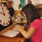 Sofia trabajando con la hora en punto del reloj material montessori.