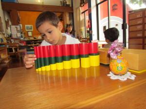 Alumno Montessori, su trabajo y concentración con los cilindros coloreados.